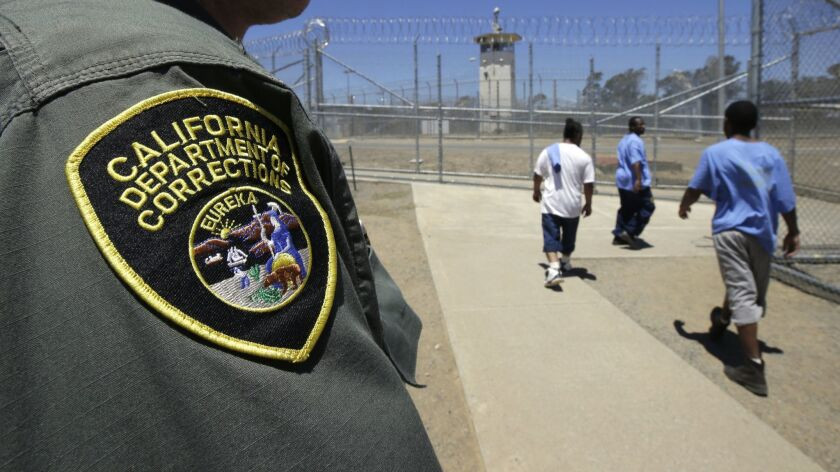 FILE - In this June 20, 2018 file photo , inmates pass a correctional officer as they leave an exer