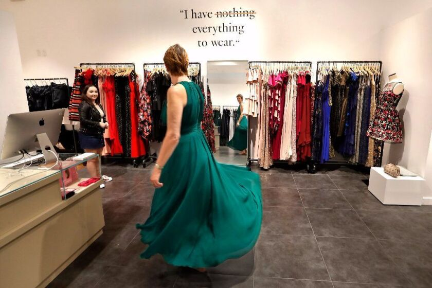 A woman tries on an evening gown in 2017 at a Rent the Runway location.