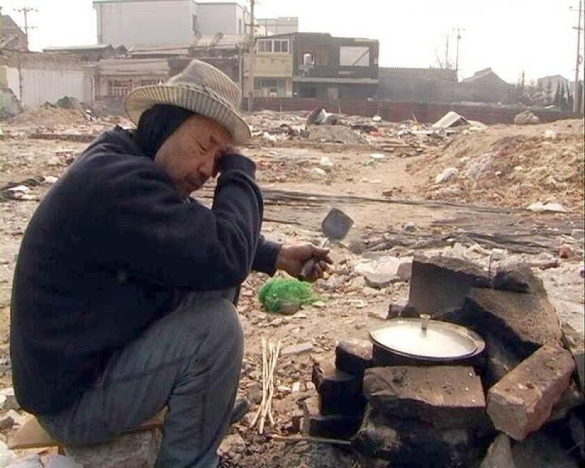 "A homeless man cooks a makeshift meal in the ruins of Qianmen, a 600-year-old Beijing neighborhood, in the documentary ""A Disappearance Foretold."""