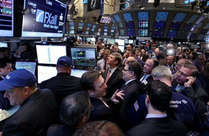 Traders gather near monitors showing the IPO of FXall, a provider of foreign exchange trading solutions, just after the opening bell Thursday, Feb. 9, 2012, on the floor of the New York Stock Exchange. U.S. stocks opened higher Thursday after Greek leaders agreed to cost-cutting measures that should prevent the country from defaulting on its debt next month. The Dow Jones industrial average pushed to within 100 points of 13,000. (AP Photo/Craig Ruttle)