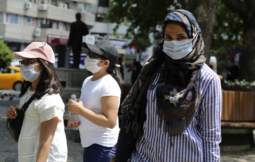 A woman and children wearing face masks to protect against coronavirus, walk in a public garden, in Ankara, Turkey, Friday, June 12, 2020. Turkey's President Recep Tayyip Erdogan revealed on Tuesday new plans to ease restrictions in place to curb the spread of the coronavirus, including the July 1 reopening of theaters, cinemas and other entertainment centers. (AP Photo/Burhan Ozbilici)