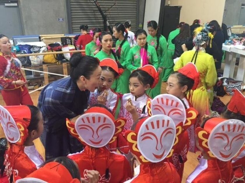 Qi Zhang speaks with her young dancers before a performance.