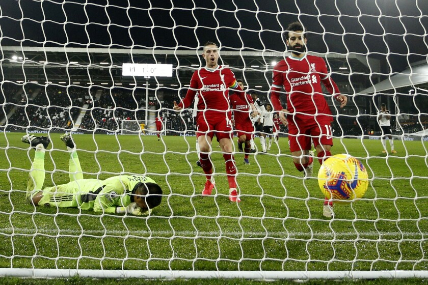 Liverpool's Mohamed Salah, right, runs to retrieve the ball after scoring from the penalty spot during the English Premier League soccer match between Fulham and Liverpool, at Craven Cottage stadium, London, Sunday, Dec. 13, 2020. (AP photo/Matt Dunham, Pool)