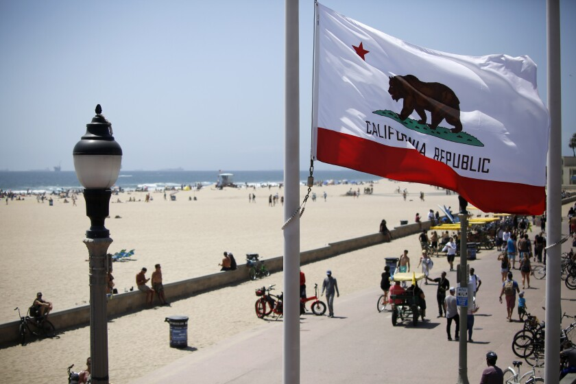 The California flag waves in the breeze as beachgoers enjoy a sunny day near the Huntington Beach Pier.