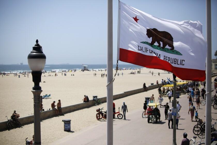 The California flag waves as beachgoers enjoy a sunny day near the Huntington Beach Pier on May 23.
