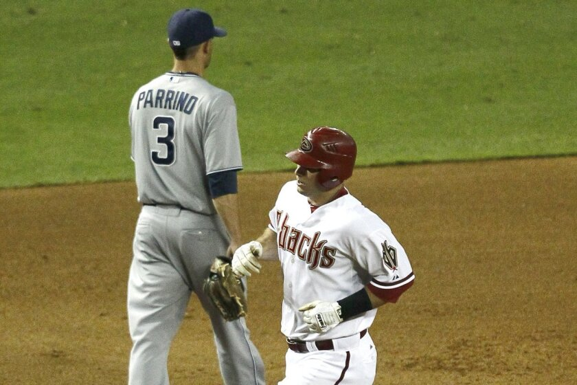 Arizona's Paul Goldschmidt rounds the bases after hitting a solo home run as the Padres' Andy Parrino walks in the opposite direction.