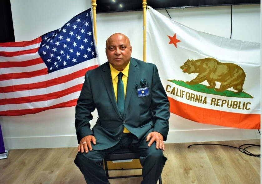 A man seated in front of California and U.S. flags