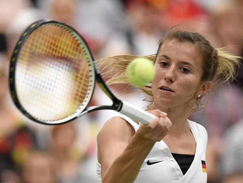 Annika Beck of Germany returns a ball to Timea Bacsinszky of Switzerland during their Fed Cup World Group first round tennis match between Germany and Switzerland  n Leipzig, Germany, Sunday, Feb. 7, 2016. (AP Photo/Jens Meyer)