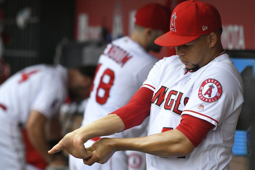 Angels pitcher Hansel Robles stretches his hand before pitching in the ninth inning against the Tampa Bay Rays on Sunday.