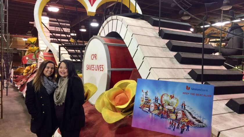 Megan Showman, left, and her mom Celine Showman inside the Pasadena barn with the under-construction float that Celine will ride in the Rose Parade on Jan. 2.
