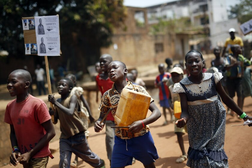 Children walk holding political placards in Bangui, Central African Republic,  Wednesday Feb. 10, 2016.  Two former prime ministers, Faustin Archange Touadera and Anicet Georges Dologuele, are running neck-and-neck in the second round of presidential elections Sunday Feb. 14 to end years of violenc