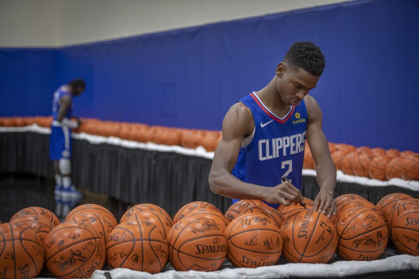 Clippers rookie guard Shai Gilgeous-Alexander (2) and teammate Montrezl Harrell sign basketball during media day in Playa Vista.
