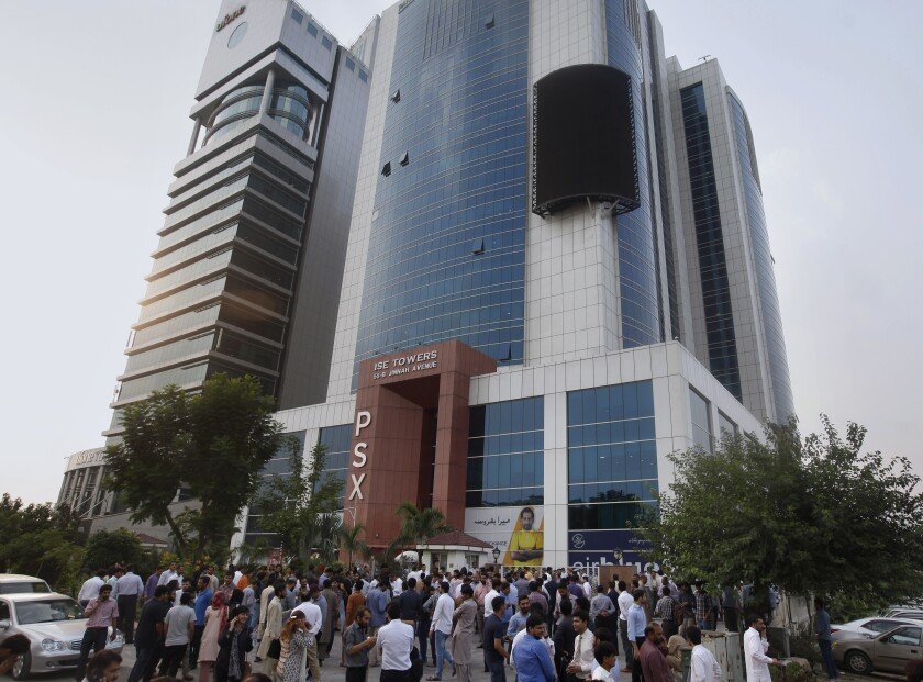 People gather outside their office building after an earthquake is felt in Islamabad, Pakistan, on Tuesday.