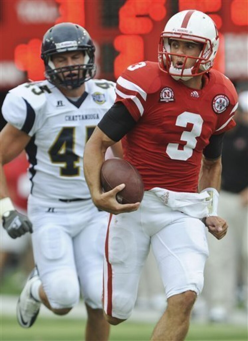 Nebraska quarterback Taylor Martinez (3) runs for a touchdown as he is chased by Chattanooga's Ryan Consiglio in the first half of their NCAA college football game in Lincoln, Neb., Saturday, Sept. 3, 2011. (AP Photo/Dave Weaver)
