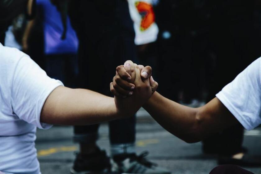 Dos manifestantes se dan la mano durante una protesta en contra de la decisión del presidente Donald Trump de suspender el programa de Acción Diferida para los Llegados en la Infancia (DACA). EFE/Archivo