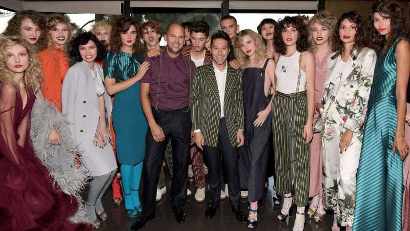 Claude Morais, center left, and Brian Wolk are surrounded by models wearing their creations backstag