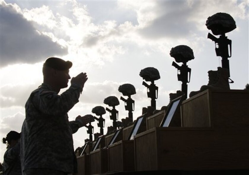 FILE - In this Nov. 10, 2009 file photo, soldiers salute as they honor victims of the Fort Hood shooting at a memorial service at Fort Hood, Texas. A memorial along a fence on the base is the only outward reminder of the worst mass shooting on a U.S. military base, as Friday, Nov. 5, 2010, marks the one-year anniversary of the shooting. (AP Photo/Donna McWilliam, File)