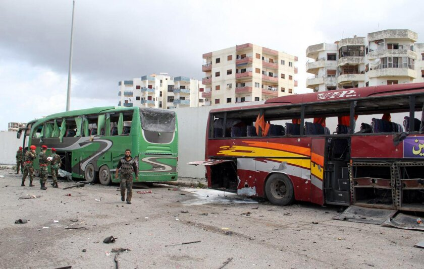 In this photo released by the Syrian official news agency SANA, Syrians soldiers inspect damaged buses at the scene where suicide bombers blew themselves up, in the coastal town of Tartus, Syria, Monday, May 23, 2016. A series of rare explosions including suicide bombings rocked coastal government strongholds in Syria Monday, killing several people and wounding dozens more, state media and opposition activists said. The Islamic State group claimed responsibility for the attacks. (SANA via AP)