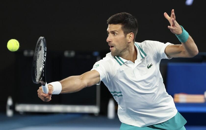 Serbia's Novak Djokovic hits a backhand return to Canada's Milos Raonic during their fourth round match at the Australian Open tennis championship in Melbourne, Australia, Sunday, Feb. 14, 2021.(AP Photo/Hamish Blair)