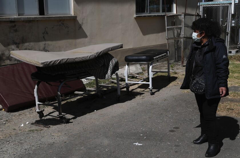 Herminia Carpio looks at the body of her brother Guillermo, covered by a slim mattress, outside a hospital in Bolivia.