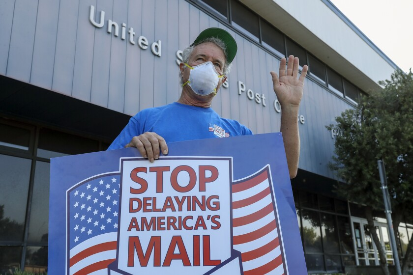 Paul Shevlin, a USPS employee, demonstrates against Postmaster General Louis DeJoy's service changes