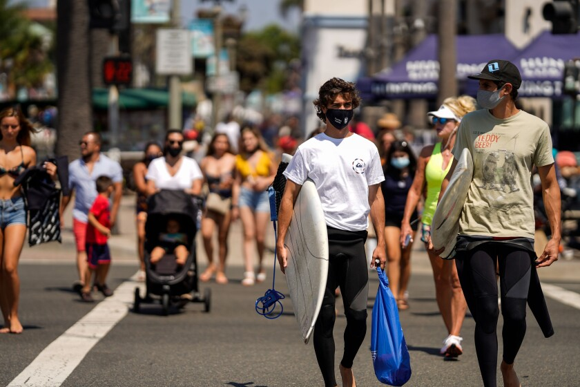 Surfers wearing face coverings in Huntington Beach