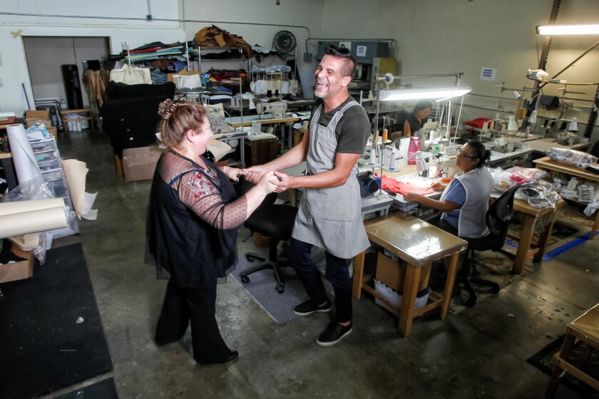 Chef Angelo Sosa (right) dances with Edith's Sewing owner Esther Cortez (left).