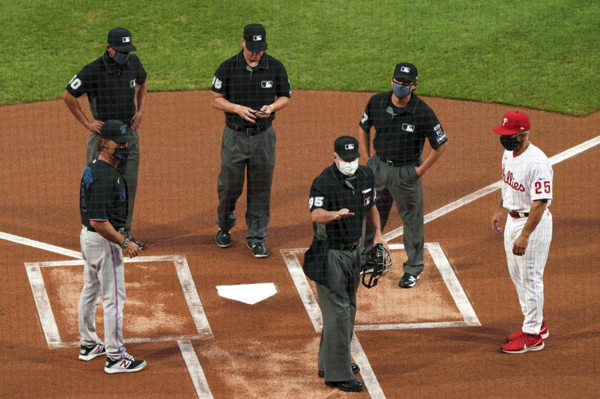 Home plate umpire Tim Timmons speaks with Marlins manager Don Mattingly and Phillies manager Joe Girardi.