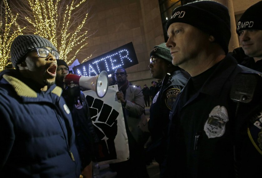 Protesters yell at police outside the Bradley Center before an NBA basketball game between the Milwaukee Bucks and the Charlotte Hornets Tuesday, Dec. 23, 2014, in Milwaukee. The group is protesting Monday's announcement that no charges against former police office Christopher Manney were filed in