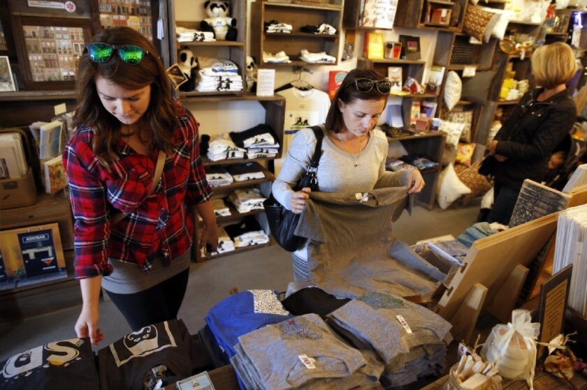 Rachel Webb, left, and Shelby Peters started their holiday shopping at Simply Local, as they and other shoppers filled boutique stores in North Park on Small Business Saturday.