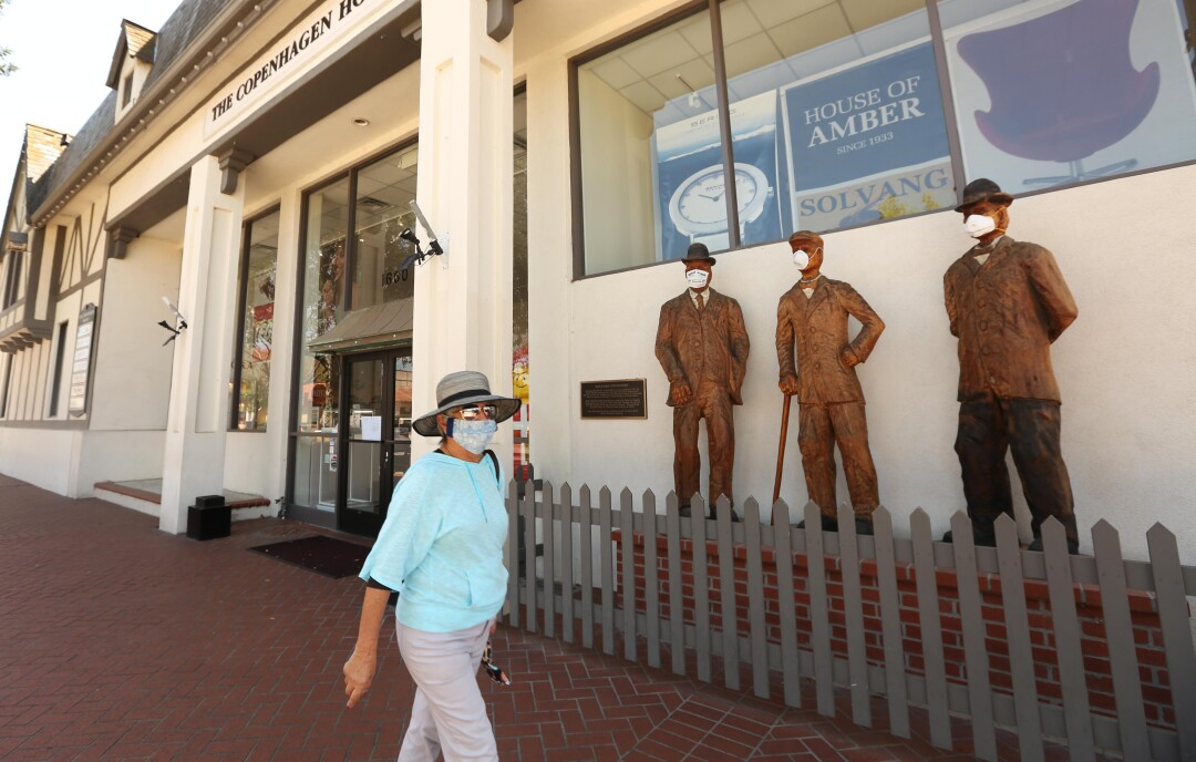 Nancy Wyatt walks past sculptures of the Solvang founders, who wear surgical masks, in front of the Copenhagen House in Solvang last week.