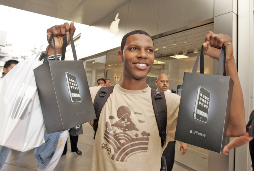 Nathan Alford shows off bags containing two iPhones he bought at the Apple store at the Westfield Century City mall on June 29, 2007.