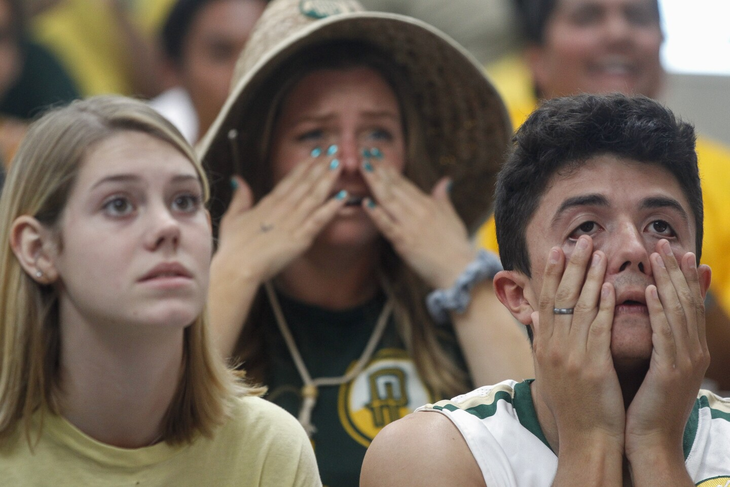 Point Loma Nazarene University students, from left, Nicole Petrie, Lindsey Peterson, and Shane Gurule, watch the hope for their team to win a NCAA Division II championship game slip away as Northwest Missouri State leads in the final seconds.