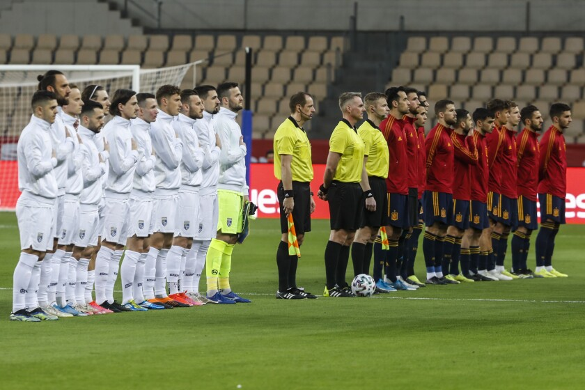 From left to right, Kosovo and Spain national team players listen national anthems prior their World Cup 2022 Group B qualifying round soccer match at La Cartuja stadium in Seville, Spain, Wednesday March 31, 2021. (AP Photo/Miguel Angel Morenatti)