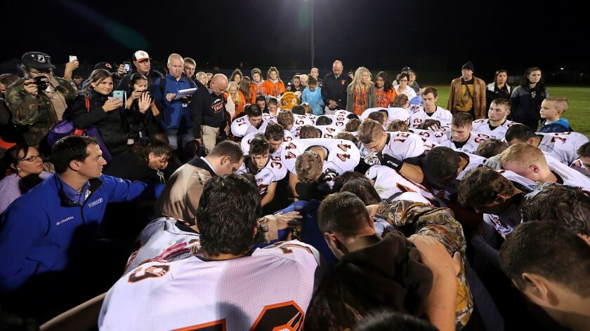 Players gather around Bremerton, Wash., High School assistant football coach Joe Kennedy, obscured in center, for prayer after a game in 2015.