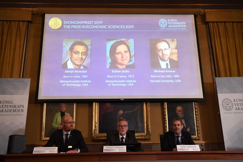 The 2019 Nobel Memorial Prize in economics winners are projected on a screen at the Royal Swedish Academy of Sciences in Stockholm on Monday. They are, from left on screen, Abhijit Banerjee, Esther Duflo and Michael Kremer.