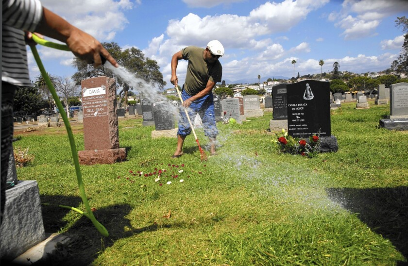 Ana Paz waters while her husband, Ryne Climaco, cuts the grass on and around the grave of a family member at Evergreen Cemetery in Boyle Heights.