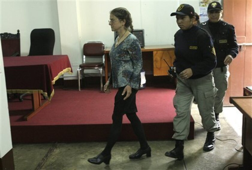 US citizen Lori Berenson, left, from New York, is escorted by police officers as she arrives for an audience at a courthouse in Lima, Peru, Friday, Nov. 5, 2010. A Peruvian judge has ordered that Berenson be released from prison on parole again. She had been paroled in May after serving three-quarters of a 20-year sentence but was returned to a Lima woman's prison in mid-August on a technicality. (AP Photo/Karel Navarro)