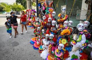 Unas personas observan piñatas alusivas para las festividades del día de muertos, el 17 de octubre de 2020, en el balneario de Acapulco en el estado de Guerrero (México). EFE/ David Guzmán