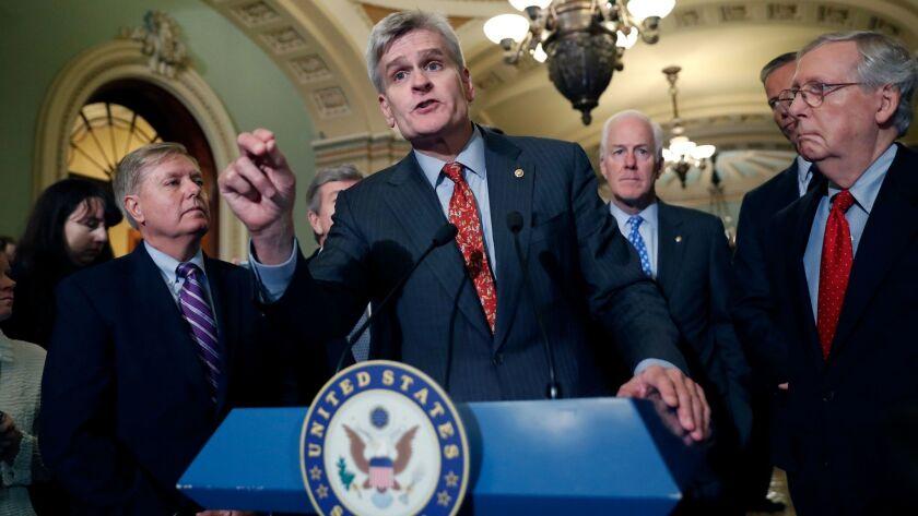 Sen. Bill Cassidy, R-La., center, speaks to the media on Capitol Hill in Washington on Sept. 19.