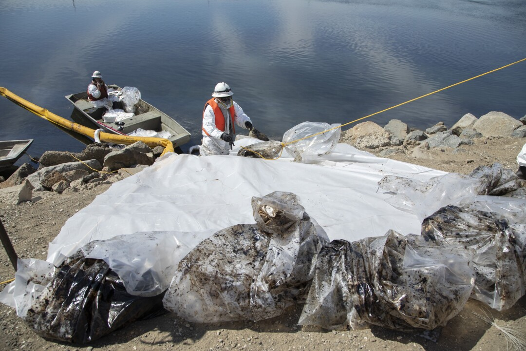 Workers with Patriot Environmental Services collect bags of oil-soaked pads and other debris during cleanup at Talbert Marsh.