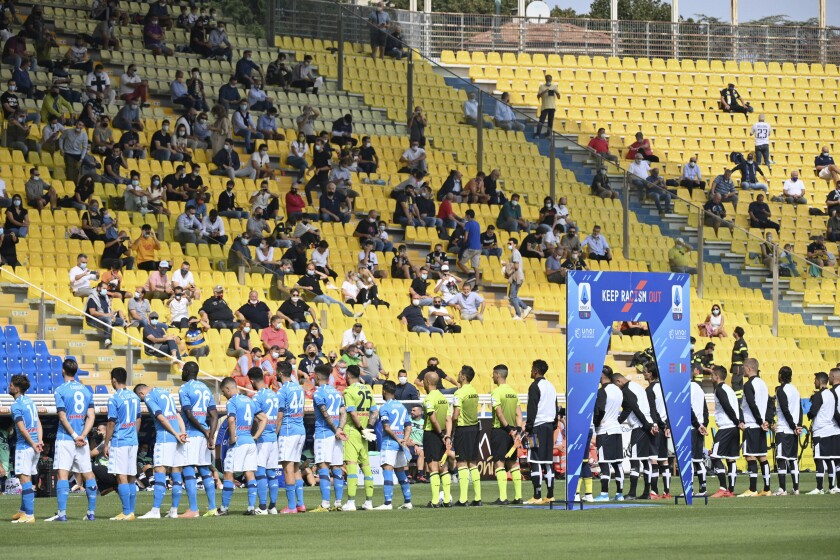 Soccer fans watch the teams line-up prior to the start of the Serie A soccer match between Parma and Napoli at the Ennio Tardini stadium in Parma Sunday, Sept. 20, 2020. Up to 1,000 fans will be allowed into stadiums for Serie A matches from Sunday. The Italian government agreed to open the stadiums to a limited number of fans following a meeting between the health and sports ministers, and other politicians, on Saturday.(Massimo Paolone/LaPresse via AP)
