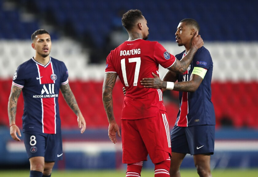 PSG's Presnel Kimpembe, right, PSG's Leandro Paredes, left, and Bayern's Jerome Boateng at the end of the Champions League, second leg, quarterfinal soccer match between Paris Saint Germain and Bayern Munich at the Parc des Princes stadium, in Paris, France, Tuesday, April 13, 2021. (AP Photo/Francois Mori)