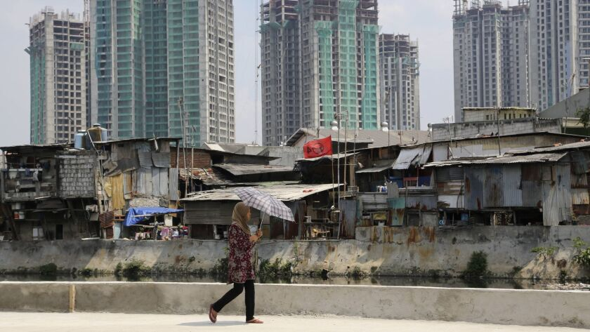 A woman walks along a city canal as new office and apartment buildings rise over a slum in Jakarta,