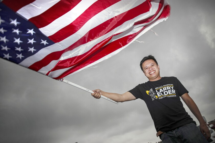 Marc Ang waves an American flag at a recall election rally in Rowland Heights in August.