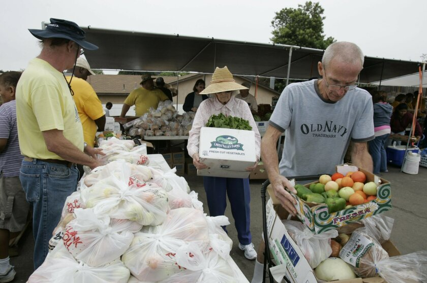 Jim Hodges, right, and his mother Vermell Hodges, 83, pick up fruits and vegetables and other staples at the Samoa Independent Church in Lemon Grove. The church is a distribution center for the San Diego Food Bank.