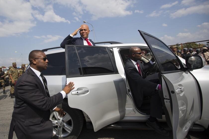 El mandatario saliente de Haití, Michel Martelly, saluda a sus partidarios antes de ingresar en su vehículo afuera del parlamento en Puerto Príncipe, Haití, el domingo 7 de febrero de 2016. Martelly pronunció el domingo su discurso de despedida ante el Parlamento. Concluyó su periodo como presidente sin un sucesor elegido que ocupe el vacío que deja su partida. Los legisladores han comenzado un proceso para conformar un gobierno interino de corto plazo. (AP Foto/Dieu Nalio Chery)