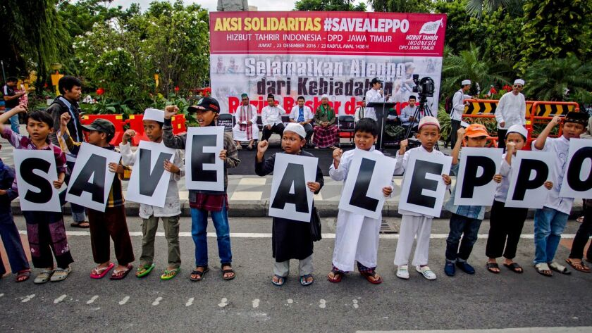 Indonesian children hold banners 'Save Aleppo' during a rally in Surabaya, East Java, Indonesia