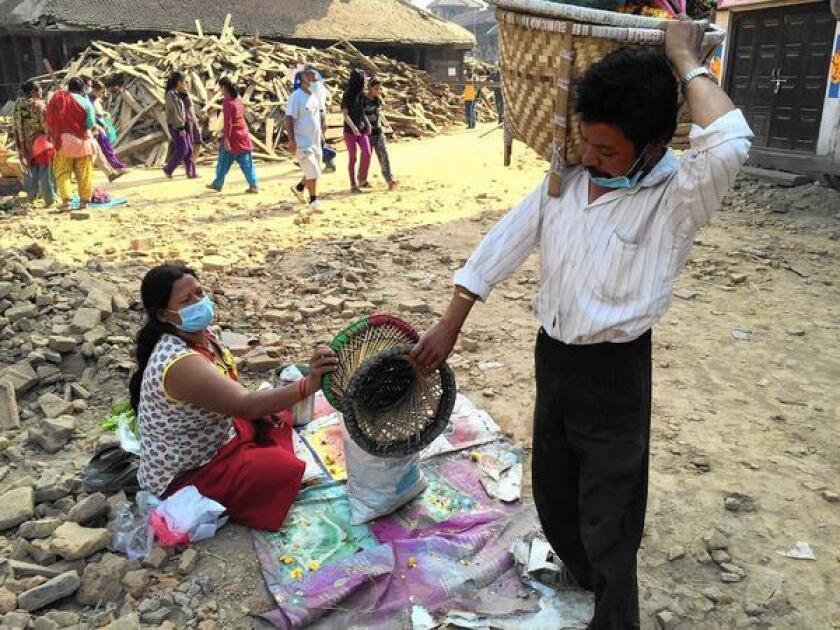 Ratna Bahadur Malatar and his wife, Mithai, work on assembling flower garlands in Katmandu's Durbar Square.