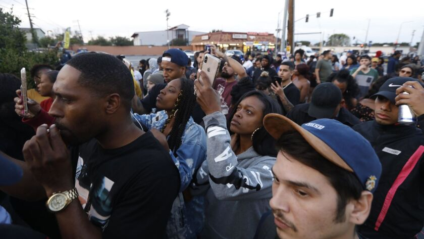 A crowd of people gathers at the scene where rapper Nipsey Hussle was killed in a shooting outside his clothing store in Hyde Park.